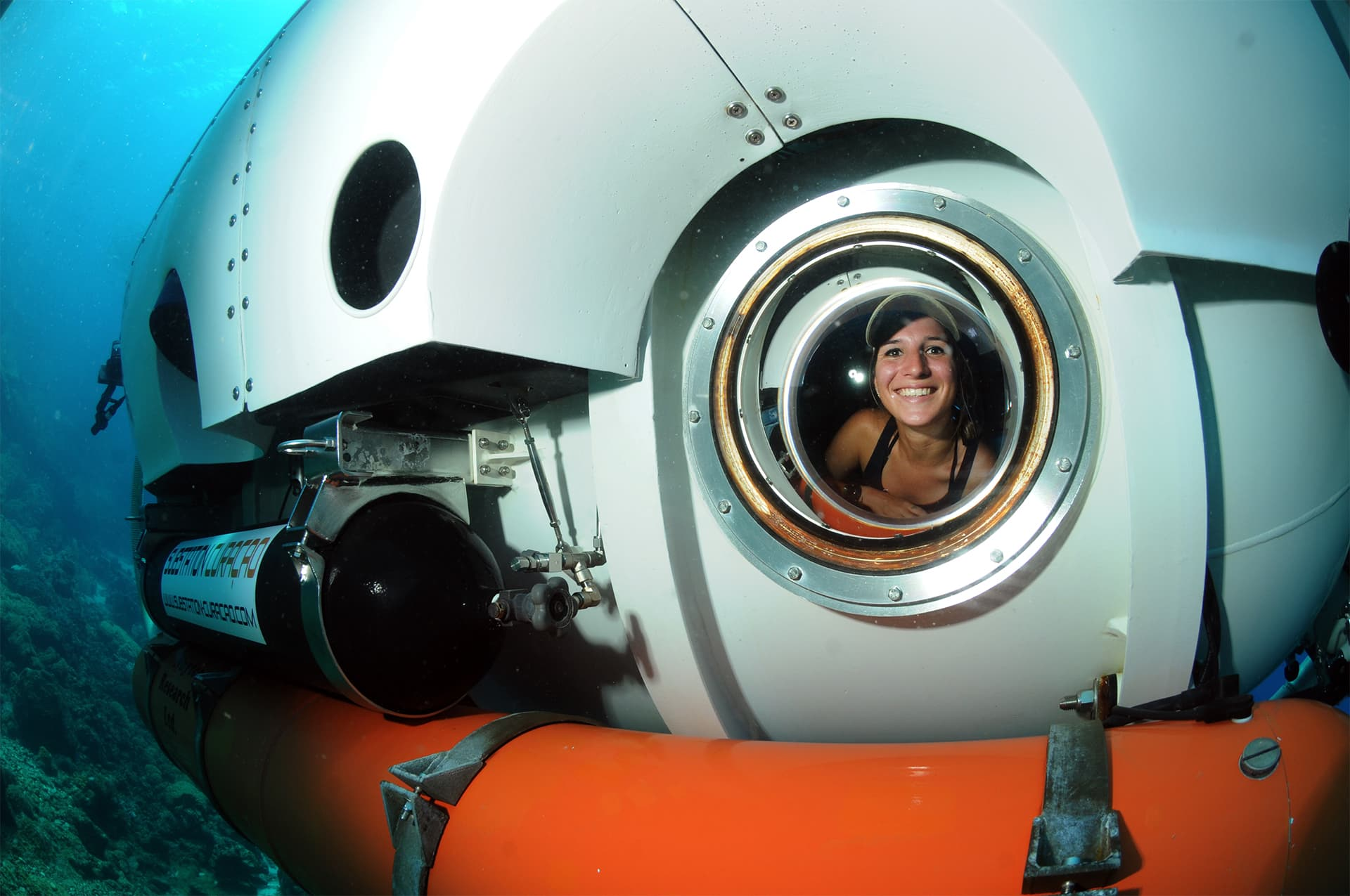 Tourist excitingly looking out from the submarine window straight into the camera while enjoying the sea life of Curaçao