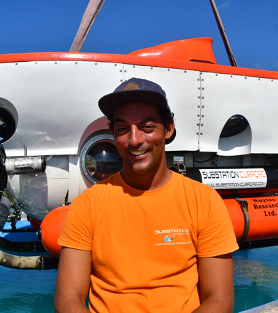 Tico Christiaan substation Curaçao pilot, captain and underwater photographer in front of curasub smiling at the camera.